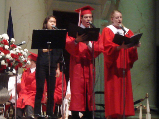 "3 people in the George Mason High School choir sing a song titled ""When You Believe"" at graduation service"